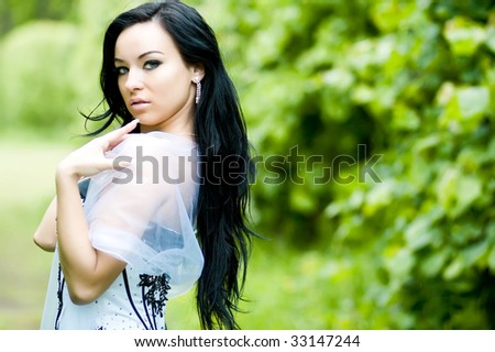 Beautiful young woman with black hair in summer park - stock photo