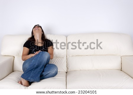 beautiful young woman with black shirt sitting in white sofa smiling - stock photo