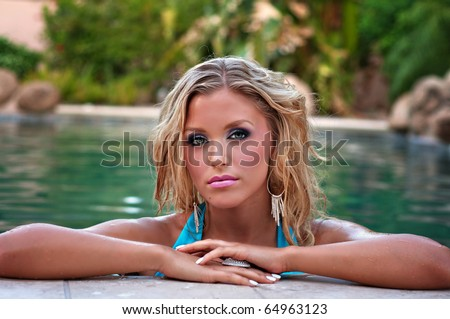 Beautiful young woman with blond hair wearing blue bikini in swimming pool