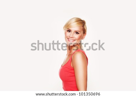 Beautiful young woman with blonde hair and a gorgeous figure smiles while wearing a tight red top. - stock photo