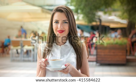 Beautiful young woman with blue eyes enjoying her cup beverage.