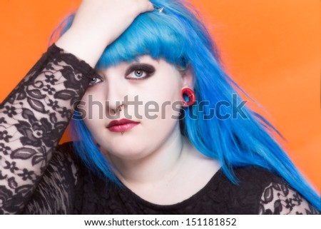 Beautiful young woman with blue hair and piercings looking at the camera - stock photo
