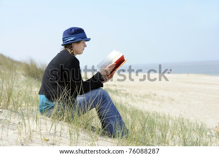 beautiful young woman with book sitting in the dunes at the beach - stock photo
