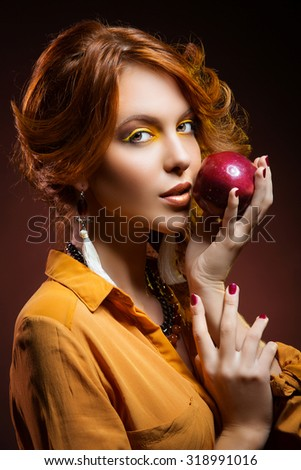 Beautiful young woman with bright yellow makeup dressed in orange autumn style holding red apple - stock photo
