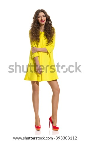 Beautiful Young Woman With Brown Curly Hair Posing In Red High Heels And Yellow Mini Dress. Full Length Studio Shot Isolated On White Background - stock photo