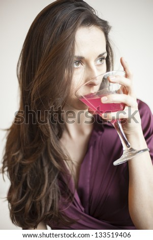 Beautiful young woman with brown hair and eyes holding a pink martini.