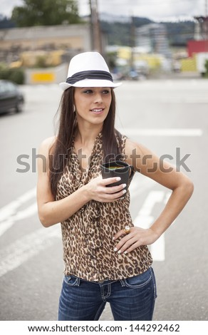 Beautiful young woman with brown hair and eyes in a leopard skin top with a black coffee cup. - stock photo