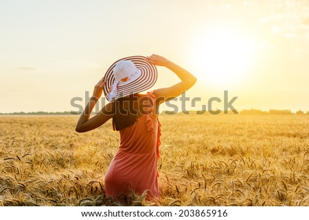 Beautiful young woman with brown hear wearing rose dress and hat with raised arms enjoying outdoors looking to the sun on perfect wheat field on sunset - stock photo