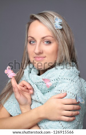 Beautiful young woman with butterflies in blue scarf - stock photo