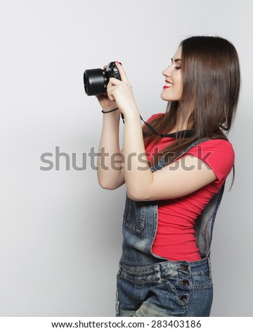 Beautiful young woman with camera over gray background