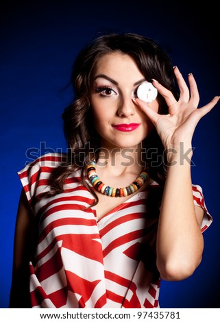 Beautiful young woman with casino chip on dark background - stock photo