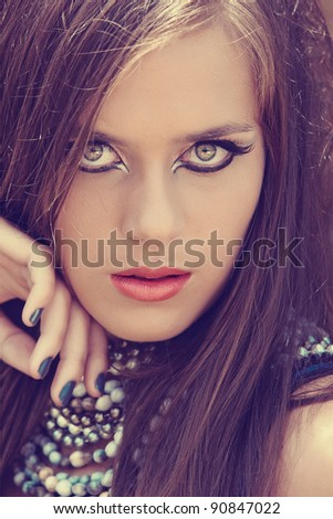 beautiful young woman with cat eye liner make-up and grey metallic manicure wear coral lipstick. - stock photo