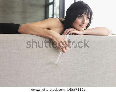 Beautiful young woman with champagne glass leaning on couch - stock photo