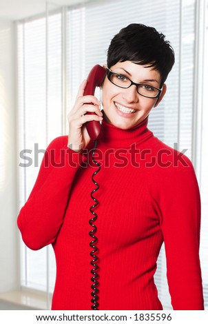 Beautiful young woman with charming big green eyes is bearing modern glasses and receiving calls on a landline phone. - stock photo