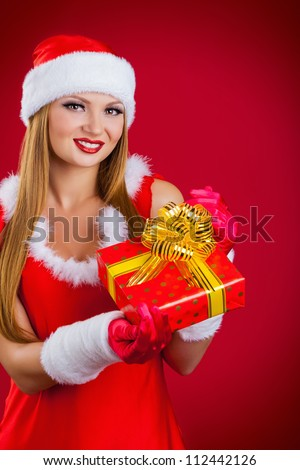 Beautiful young woman with Christmas present on a red background