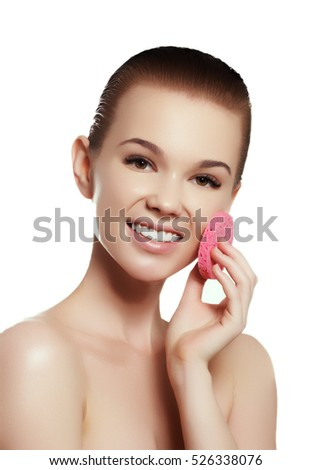 Beautiful young woman with clean fresh skin touch own face. Facial treatment . Cosmetology , beauty and spa. Smiling young girl cleaning her face with cotton disc