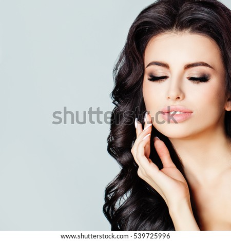 Beautiful Young Woman with Clean Fresh Skin touching her Hand Her Face. Beauty, Facial Treatment and Cosmetology