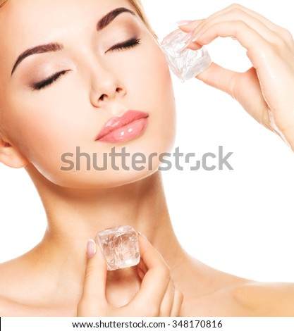Beautiful young woman with closed eyes applies the ice to face - isolated on white.