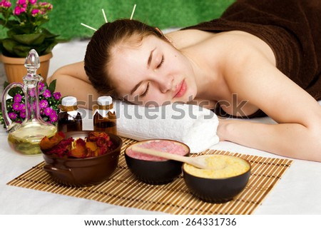 Beautiful young woman with closed eyes at a spa salon - stock photo