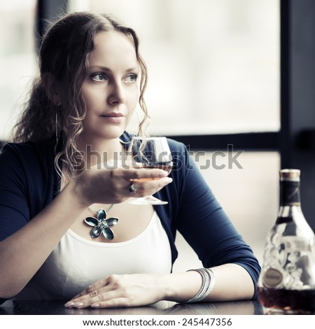 Beautiful young woman with cognac at restaurant  - stock photo