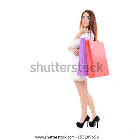 beautiful young woman with colored shopping bags over white background, full length portrait - stock photo