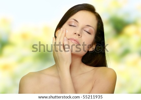 Beautiful young woman with cream. - stock photo