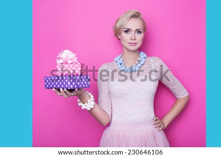 Beautiful young woman with cream colored dress holding pink and purple gift boxes. Studio portrait over bright pink background with blue edge - stock photo