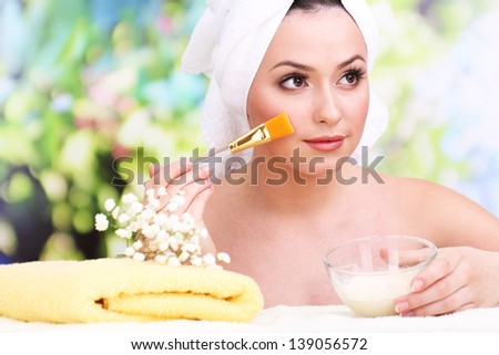 Beautiful young woman with cream for face mask towel on her head on bright background - stock photo