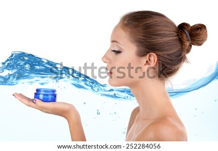 Beautiful young woman with cream on abstract blue water wave background - stock photo