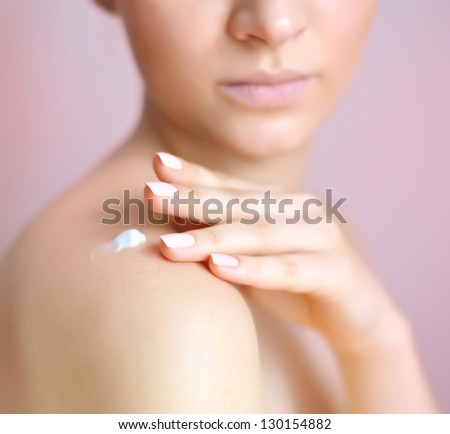 Beautiful young woman with cream on her shoulder. Focus is on a hand - stock photo