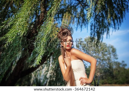 Beautiful young woman with creative fashion hairstyle. Spanish flamenco hairstyle. Creative makeup. Shooting outdoor - stock photo