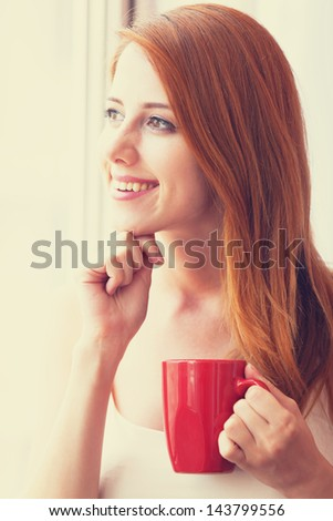 Beautiful young woman with cup over window. - stock photo