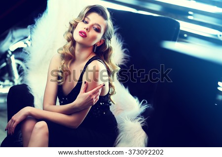 beautiful young woman with curly blond hair and bright makeup. Fashion studio shot. Retro fashion - stock photo