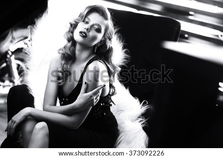 beautiful young woman with curly blond hair and bright makeup. Fashion studio shot. Retro fashion. Black and white image - stock photo