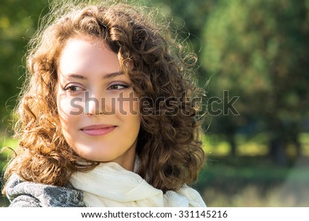 Beautiful young woman with curly hair posing outdoors - stock photo