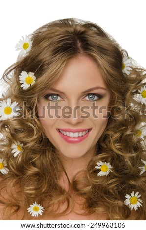 Beautiful young woman with daisies in curly hair - stock photo