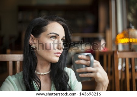 Beautiful young woman with dark brown hair and eyes holding a gray coffee cup. - stock photo