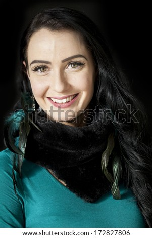 Beautiful young woman with dark brown hair and eyes on a black background. - stock photo