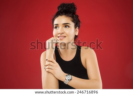Beautiful young woman with dark curly hair and perfect skin, with a watch at hand. on a red background - stock photo