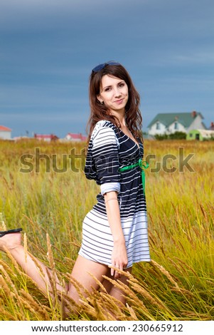 beautiful young woman with dark hair in the summer on the meadow with green grass - stock photo