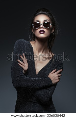 Beautiful young woman with dark lips in black sparkling dress and fancy sunglasses over grey background - stock photo