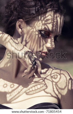 beautiful young woman with dramatic red eyeshadows and false lashes with lace shadow over her face - stock photo