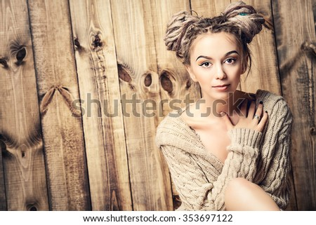 Beautiful young woman with dreadlocks hairstyle posing over wooden wall. Beauty, fashion. Hairstyle. Make-up. - stock photo