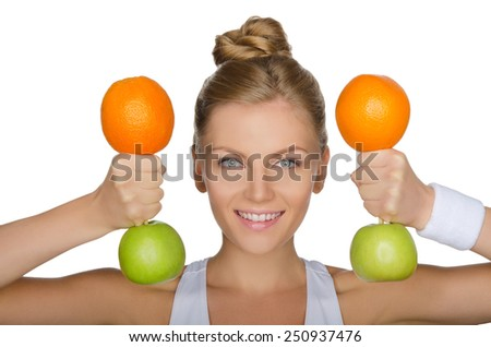 Beautiful young woman with dumbbells from apples and oranges isolated on white - stock photo