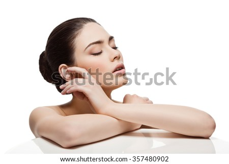 Beautiful young woman with eyes closed touching face. Isolated over white background. Copy space. - stock photo
