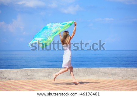 beautiful young woman with fabric running on quay - stock photo