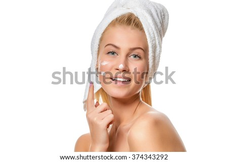 Beautiful young woman with facial cream on her nose, cheek  - stock photo