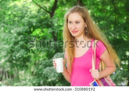 Beautiful young woman with fair wavy hair, smiling, holding paper cup of takeaway drink in her hand, outdoor in summer. Blurred green background, space for text, horizontal format image
