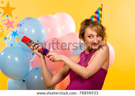 Beautiful young woman with firecracker indoors - stock photo