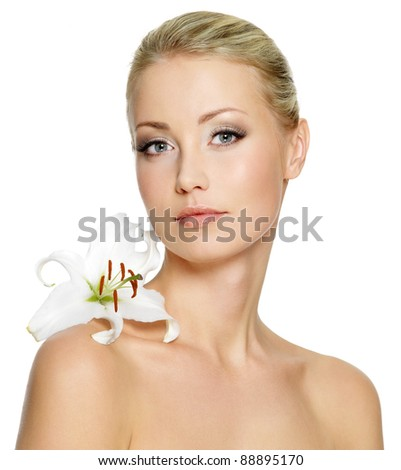 Beautiful young woman with fresh clean skin and white flower on shoulder - isolated